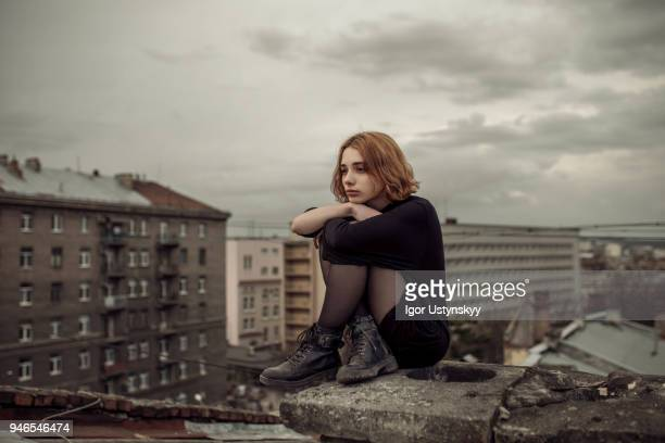 young woman posing on the roof - hugging knees stock pictures, royalty-free photos & images