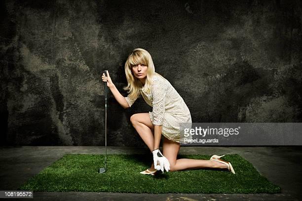 junge frau posieren auf rasen gras mit golf club - golf lustig stock-fotos und bilder