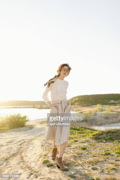 young woman posing outdoors - skirt blowing stock photos and pictures
