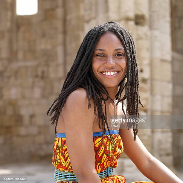Young woman posing outdoors, smiling
