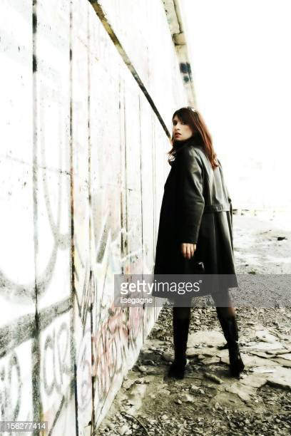 young woman posing outside grunge building - black alley stock photos and pictures