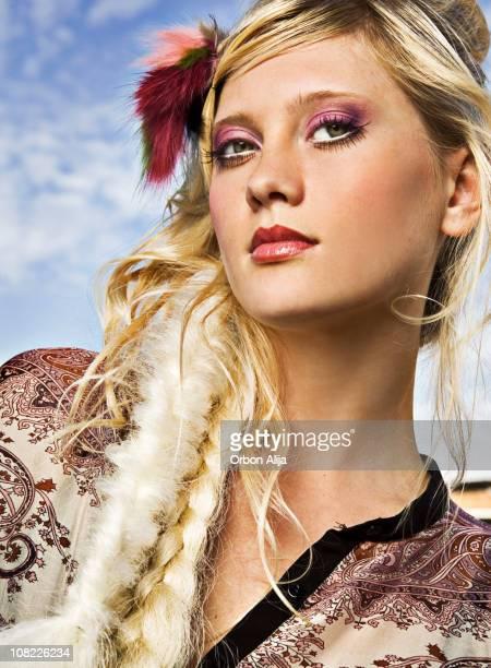 Junge Frau posieren außerhalb mit geflochtener Zopf und Blumen in den Haaren