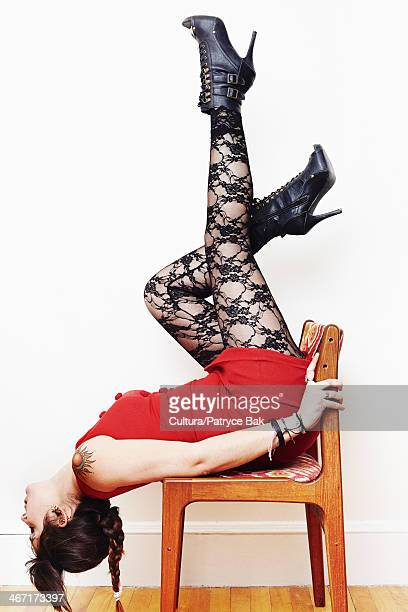 Young woman posing upside down on a chair