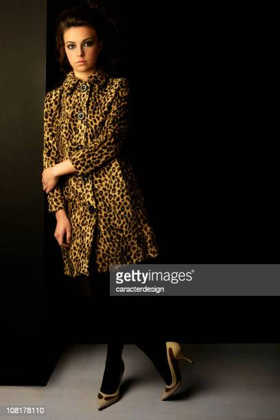 young woman posing wearing leopard fur coat - animal pattern stock pictures, royalty-free photos & images