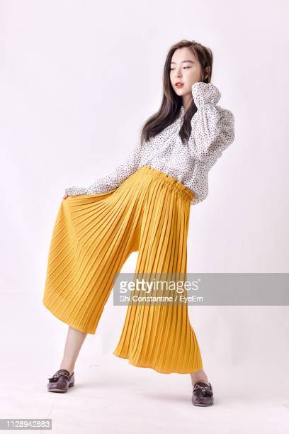 young woman posing while standing against white background - fashion model photos et images de collection
