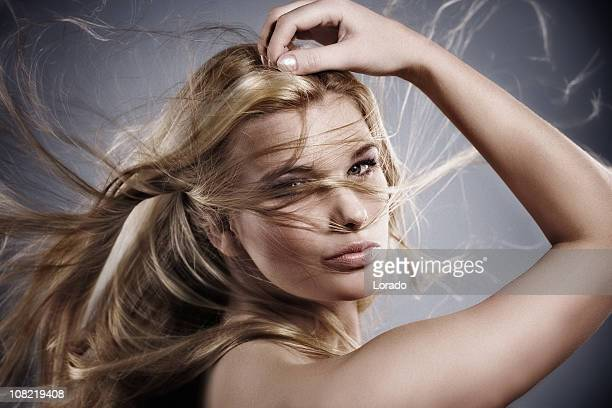 Jeune femme posant avec les cheveux dans le vent