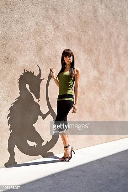Young Woman Posing with Her Dragon Shaped Shadow on Wall
