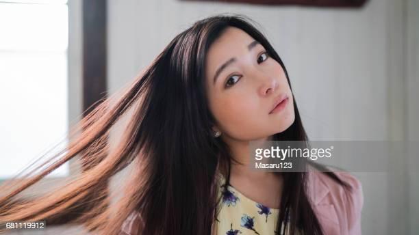 若い女性が彼女の髪を持つポーズを広げる