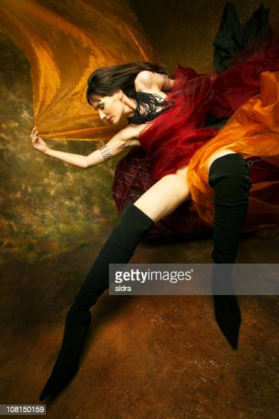 Young Woman Posing with Red and Orange Silk Fabric