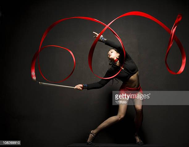 young woman posing with ribbon doing rhythmic gymnastics - rhythmic gymnastics stock pictures, royalty-free photos & images