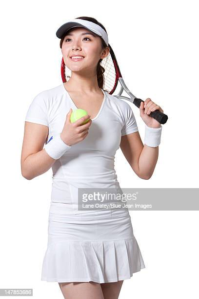 Young woman posing with tennis ball and racket