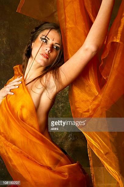 Joven mujer posando envuelto en Orange tela de seda
