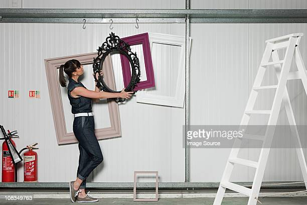 Young woman positioning picture frame