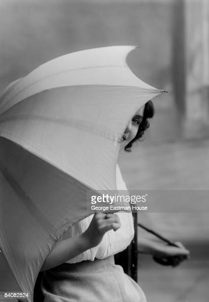 Young woman, possibly the English-born actress Daisy Elliston, peeks around the umbrella she playfully holds in front of her, ca.1918. Great Britain.