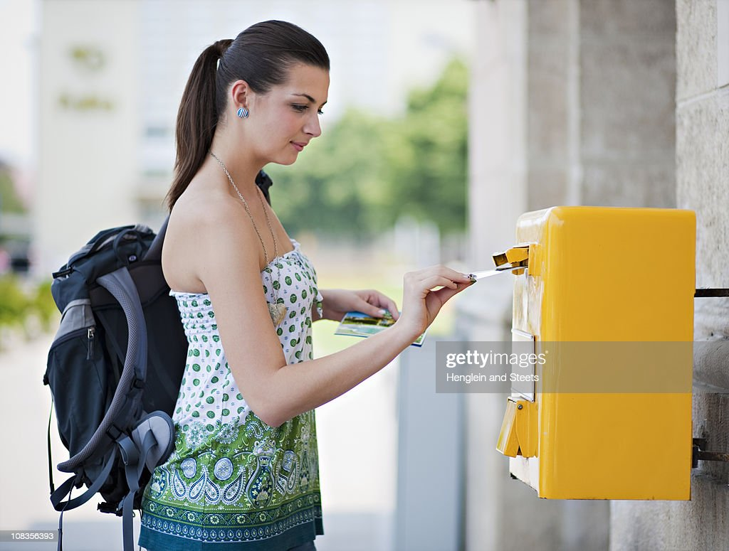 Young woman posting postcard : Bildbanksbilder