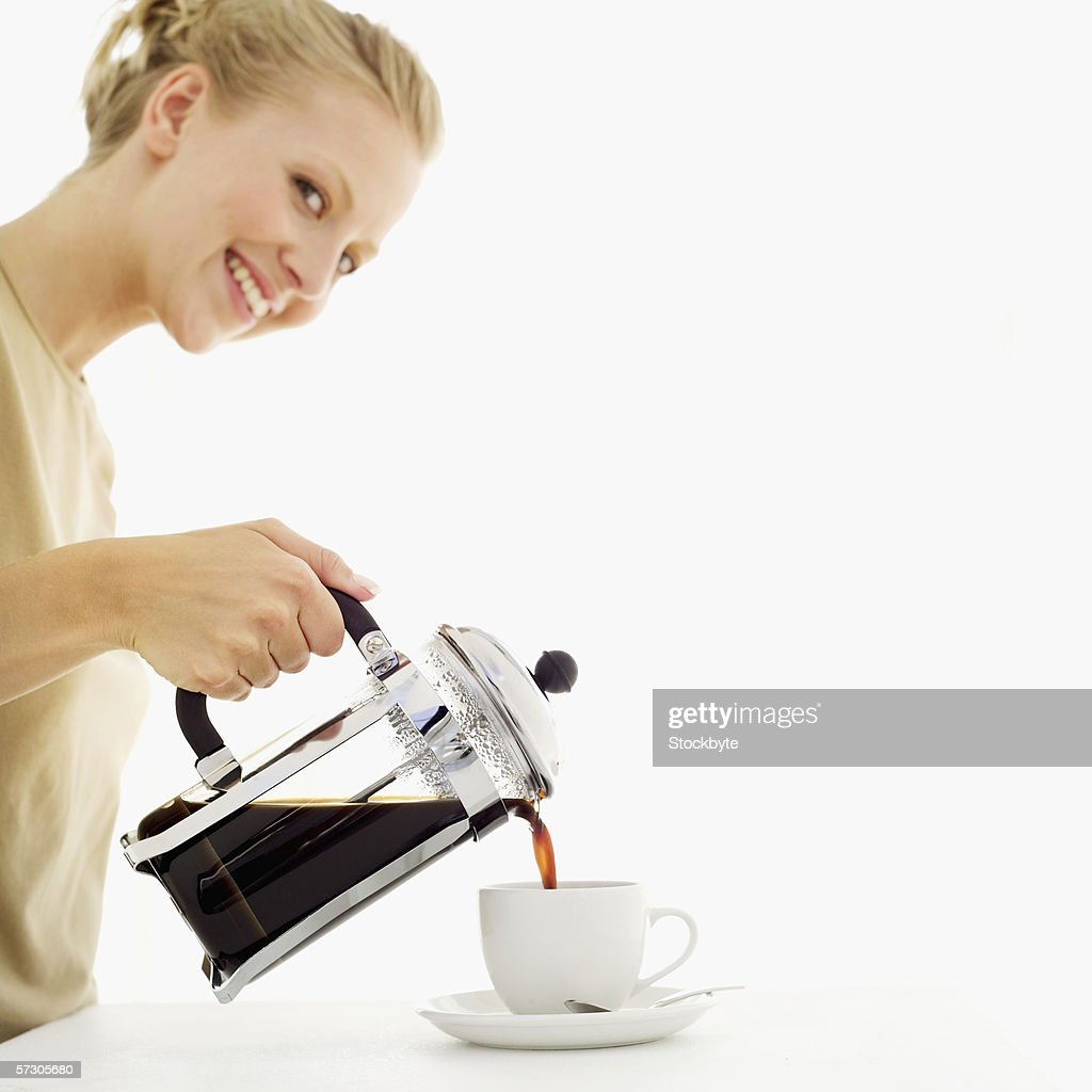 Young woman pouring coffee from a coffee press into a cup : Stock Photo