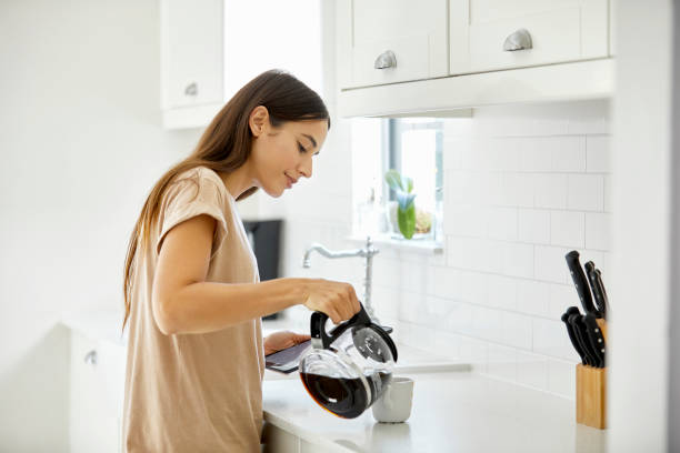 young woman pouring coffee in cup at home - preparation stock pictures, royalty-free photos & images