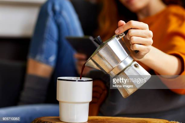 young woman pouring coffee into cup at home - cafe imagens e fotografias de stock