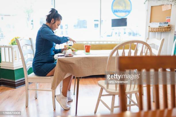 young woman pouring dressing over salad - mini dress stock pictures, royalty-free photos & images