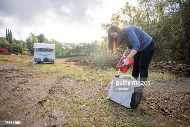 young woman pouring gas into the generator at camp - generator stock pictures, royalty-free photos & images