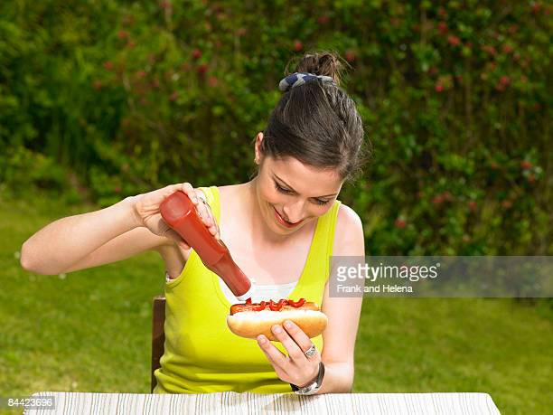 Young woman pouring ketchup onto hot dog
