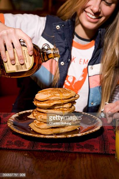 Young woman pouring maple syrup on stack of pancakes, smiling
