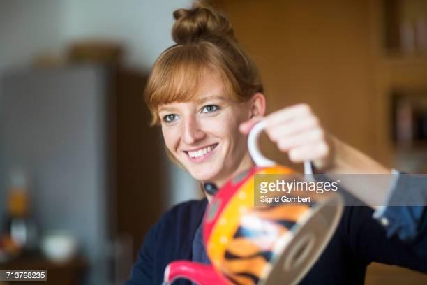young woman pouring tea from teapot - sigrid gombert - fotografias e filmes do acervo