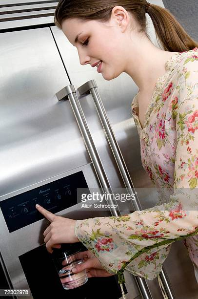 Young woman pouring water from a refrigerator water dispenser into a glass