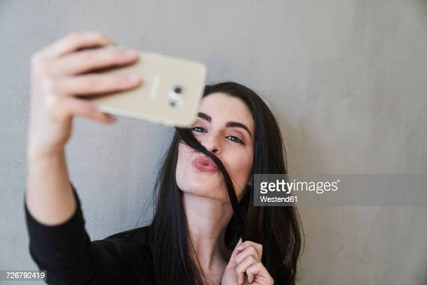 young woman pouting taking a selfie - hair love stock pictures, royalty-free photos & images