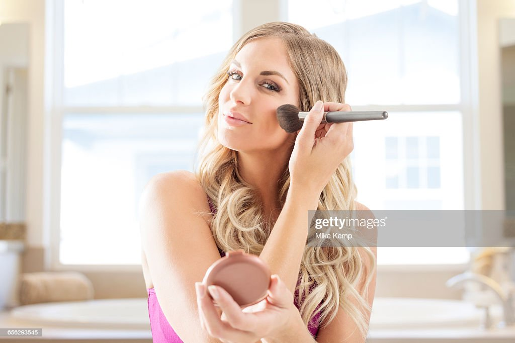 Young woman powdering face in bathroom : Stock Photo