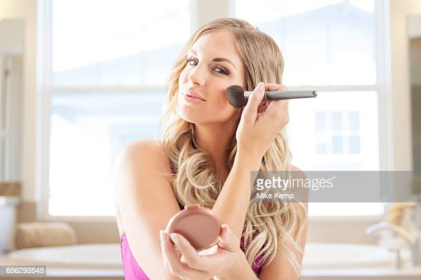 Young woman powdering face in bathroom