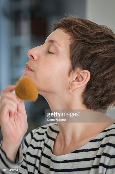 young woman powdering her face - dorte fjalland stock-fotos und bilder