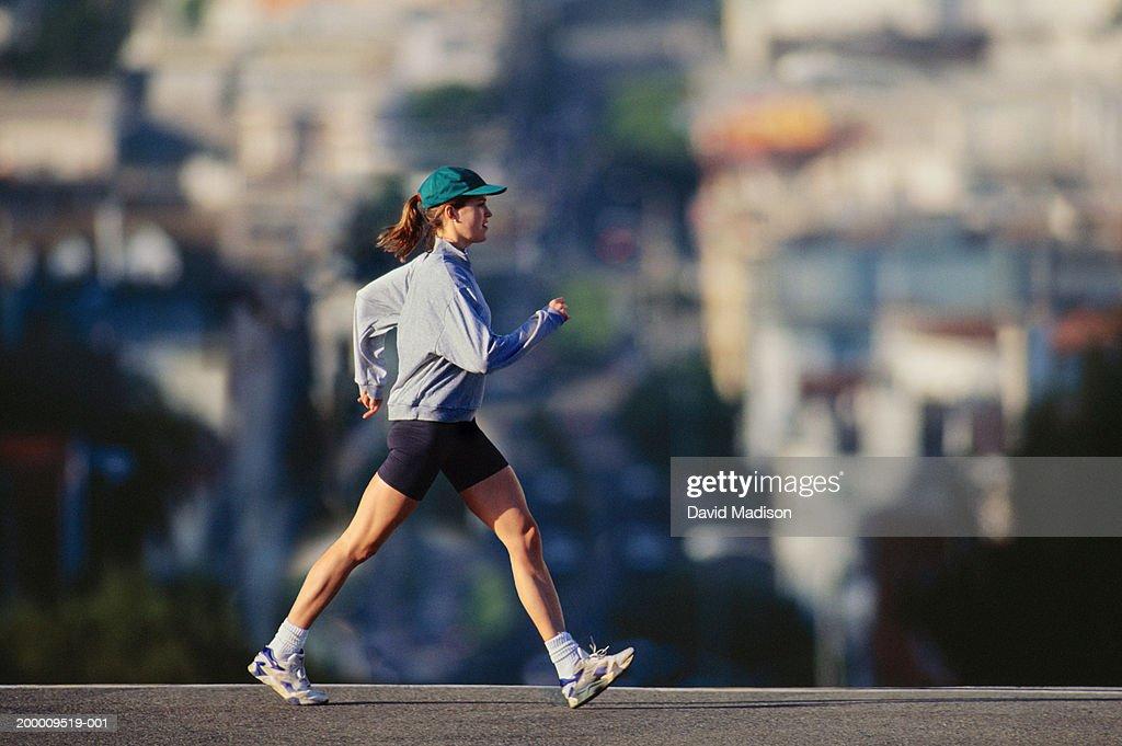 Young woman powerwalking in urban area, profile : Stock Photo