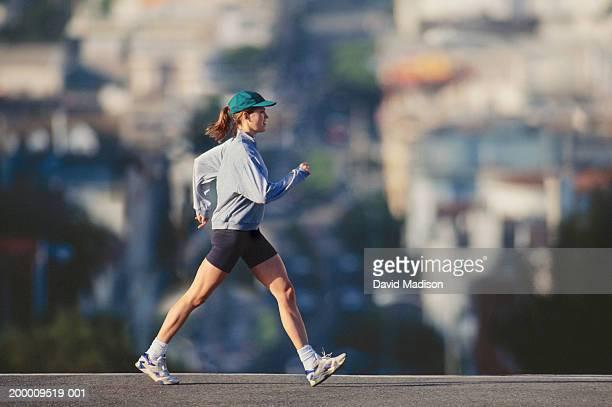 Young woman powerwalking in urban area, profile
