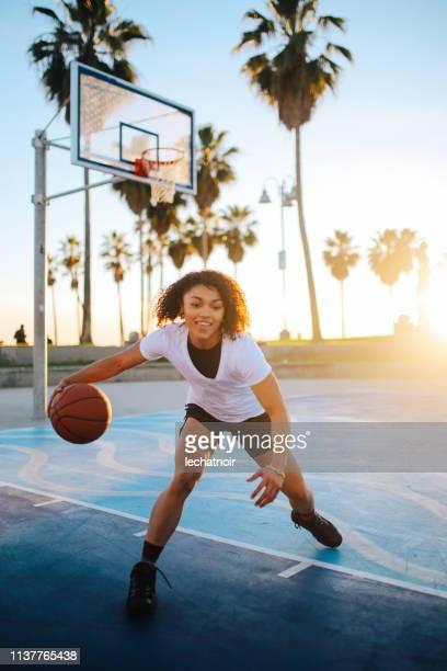 young woman practice basketball dribble in venice, california - giocatore di basket foto e immagini stock