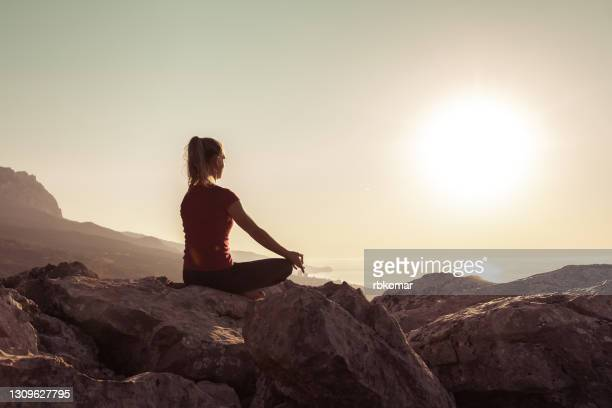 young woman practices yoga and meditates on the mountain - buddhism stock pictures, royalty-free photos & images