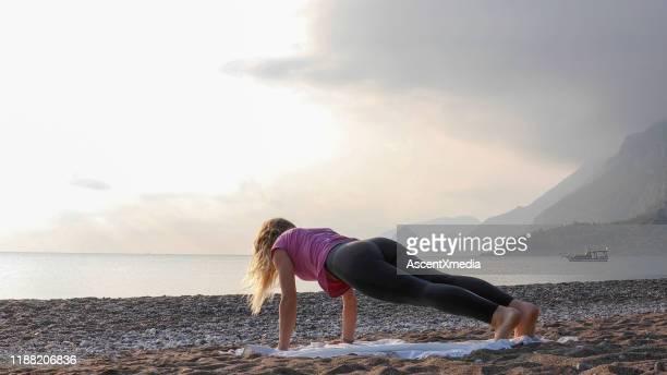 giovane donna pratica yoga sulla spiaggia - vivere semplicemente foto e immagini stock