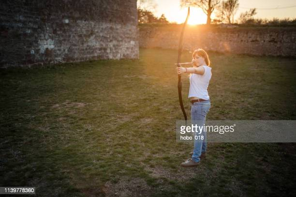 young woman practicing archery, shooting with a longbow - longbow stock photos and pictures