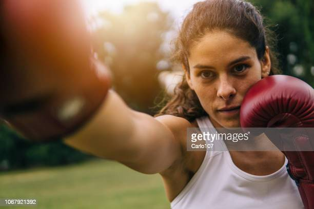 young woman practicing boxe outdoors - martial arts stock pictures, royalty-free photos & images