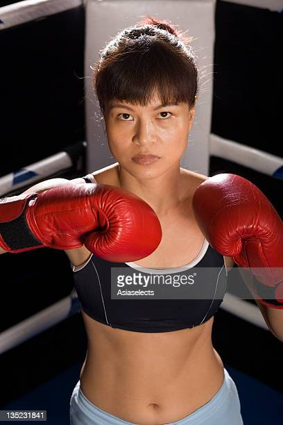 young woman practicing boxing in a boxing ring - belly punch stock pictures, royalty-free photos & images