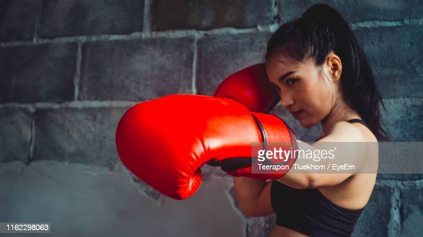 young woman practicing boxing wall - punching stock pictures, royalty-free photos & images