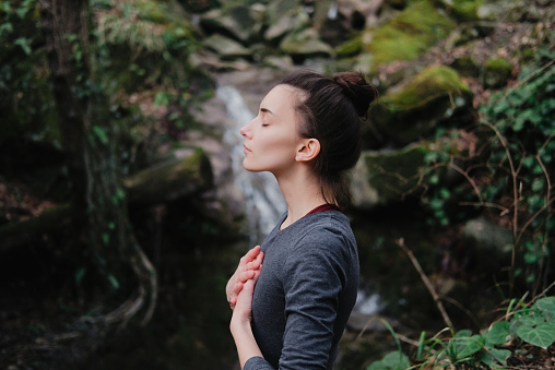 Young woman practicing breathing yoga pranayama outdoors in moss forest on background of waterfall. Unity with nature concept. 1171968887