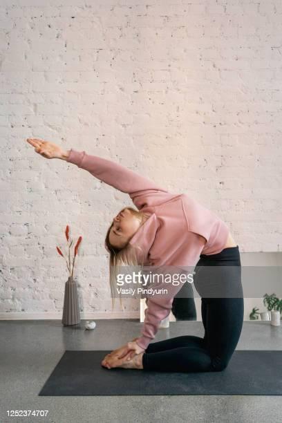young woman practicing camel pose backbend in yoga studio - camel active stock-fotos und bilder