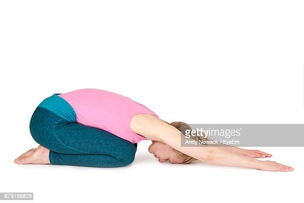 young woman practicing childs pose against white background - childs pose stock photos and pictures