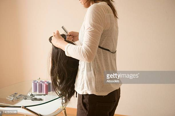 young woman practicing hair dressing - wig stock pictures, royalty-free photos & images