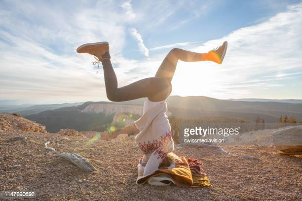 young woman practicing headstand yoga pose in nature at sunset; girl in the usa enjoying nature and relaxation exercises in bryce canyon - rock hoodoo stock pictures, royalty-free photos & images