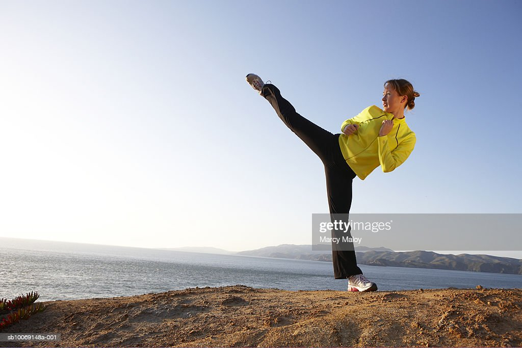 Young woman practicing high kick on shore : Stockfoto