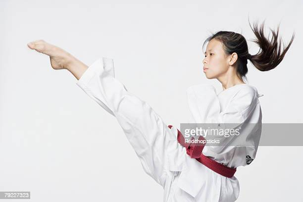 Young woman practicing kicking