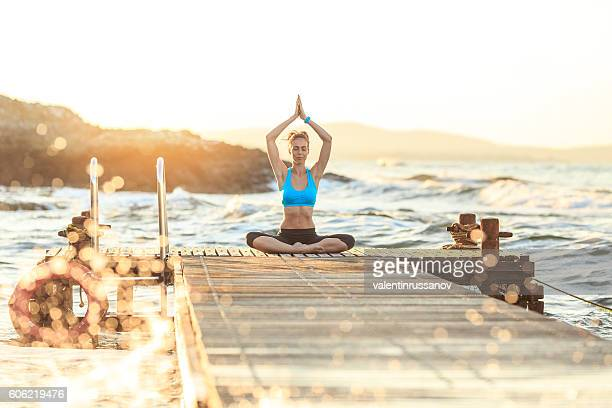 Young woman practicing lotus position on pier