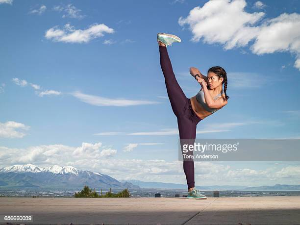 Young woman practicing martial arts outdoors